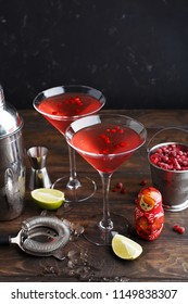 Two glasses of Cosmopolitan cocktail with frozen cranberries, slices of lime, crushed ice and small Matreshka on wooden table