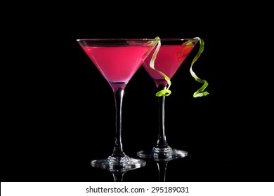 Two glasses of cosmopolitan cocktail on a black background.