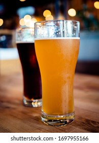Two glasses of craft fresh brewed beer light and dark standing on a raw grungy wooden table with a blurred background with bokeh bubbles.