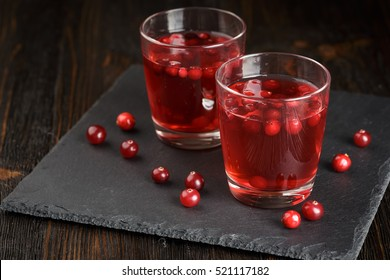Two glasses of cranberry cocktail on a black stone