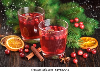 Two glasses of cranberry drink, cranberries, cinnamon sticks, anise stars and dried slices of orange on a wooden background.