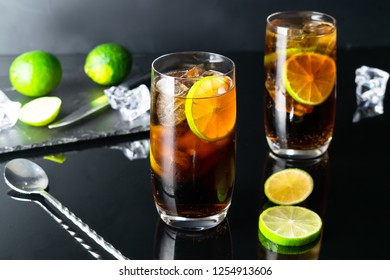 Two glasses of Cuba Libre Cocktail, with white rum, cola, garnished with 2 lime slices, in highball glass filled with ice. Bar spoon, lime and ice cubes in a dark background