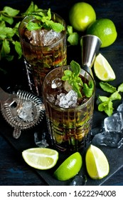 Two glasses of Cuba libre  cocktail with fresh lime and mint on  dark table, holidays party concept