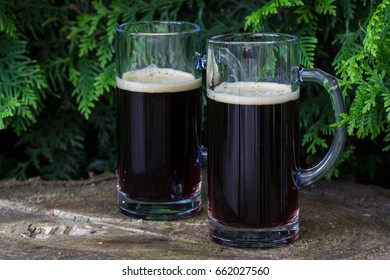 Two glasses of dark beer on wooden background. Midsummer in Latvia. Celebration of traditional Ligo feast in June