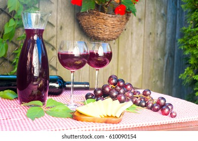 Two glasses, decanter and bottle with homemade red wine, some grape, and cheese on table in garden at sunny day outside. Horizontal vibrant colored image with vintage filter. Wooden background
