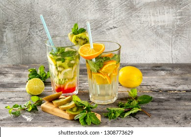 Two glasses of detox water with lemon, kiwi, orange and mint at concrete decorated table background. Concept of healthy lifestyle.