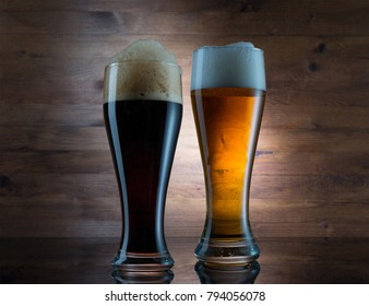 Two glasses of different colored beer on wooden background