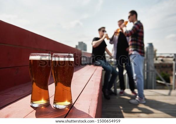 背景に野外のパブ、コピー用スペース、コピー用スペースに、ぼかしたビールと男性の友達の2人。友情と祝賀のコンセプト
