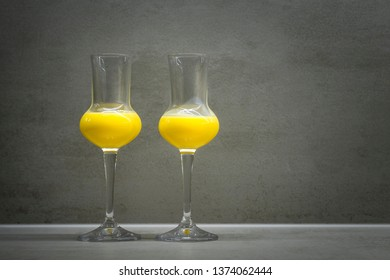 Two glasses of egg liqueur on grey texture background