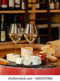 Two glasses of expensive french white wine served in parisien bar. Accompanied by delicious plate with various traditional local artisan cheese,  freshly baked bread. Cozy atmosphere, warm light