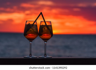 Two glasses of the famous Italian cocktail aperol  spritz  against the background of sunset.
