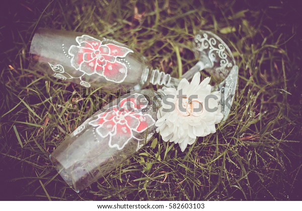 Two glasses with flowers and wedding rings on the grass. Wedding accessories