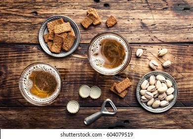 Two glasses of fresh beer and salty snacks on a brown wooden table, top view