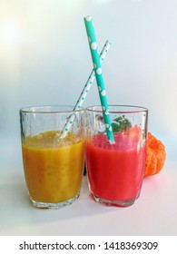 Two glasses of fresh juice with tubes. Summer and tropical smoothies. Cold blended drinks, fruit smoothie.