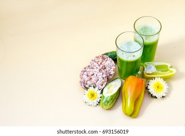 Two glasses of freshly prepared cucumber smoothies next to the ingredients