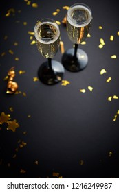 Two glasses full of sparkling champagne wine with golden decoration of confetti and serpentines on black elegant background. Top view with copy space. Festive or party concept.