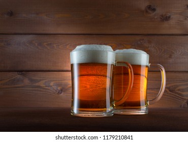 Two glasses of golden beer on wooden background