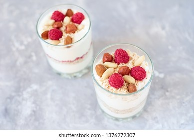 Two glasses of greek yogurt granola with raspberries, oatmeal flakes and nuts, top view. Healthy nutrition