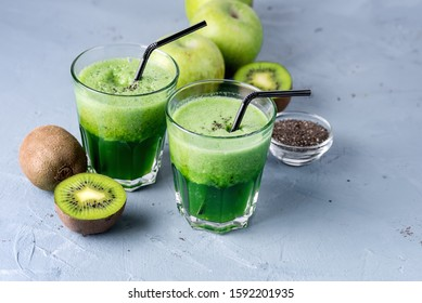 Two Glasses of Healthy Green Kiwi Green Apple and Chia Seeds Juice Detox Smoothie Diet Drink Blue Background