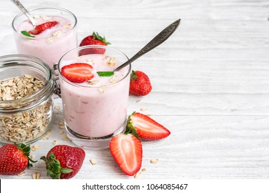 two glasses of healthy strawberry yogurt with fresh berries, oats spoon and mint on white wooden table. healthy breakfast. close up with copy space