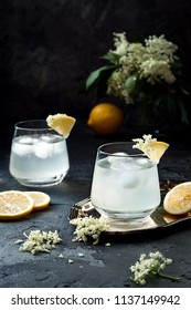 Two glasses of homemade elderflower gin sour or lemonade garnished with freshly picked elderflowers.