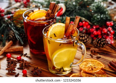 Two glasses of hot mulled wine with oranges and spices on wooden background. Close-up side view.