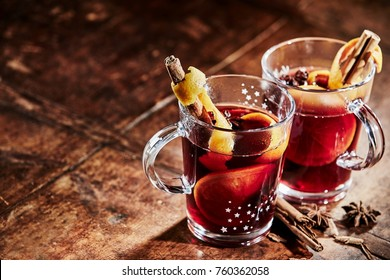 Two glasses of hot spicy Gluhwein to celebrate Christmas with stick cinnamon and star anise on a rustic wooden table with copy space