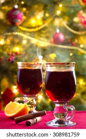 Two glasses of hot, steaming mulled wine with Christmas tree in background