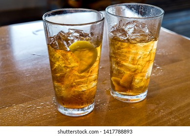 Two glasses of ice cold chilled ice tea with lemon wedge.