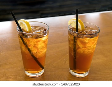 Two glasses of ice cold chilled refreshing ice tea with lemon wedge and straws.