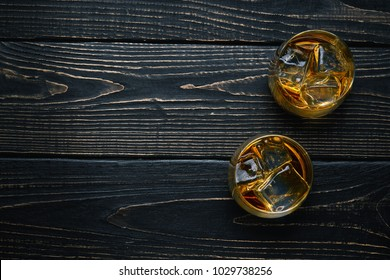 Two glasses with ice and whiskey  on a  black wooden table.Top view