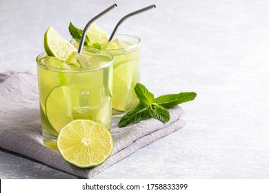 Two glasses with iced green matcha tea with lime, ice, fresh mint and metal drinking straws on grey napkin on light grey backdrop. Healthy food, No Plastic, Zero Waste concepts. Copy space for text.