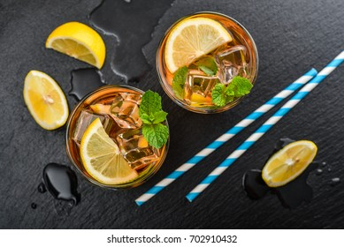 Two glasses of iced sweet tea with lemon and mint and retro paper straws on black slate background, top view