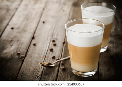 Two glasses of latte coffee beans and spoon on old wooden table.