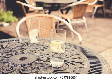 Two glasses with lemon on a table in a garden