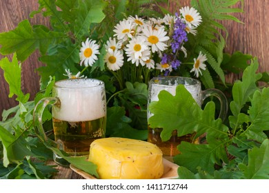 Two glasses of light beer with cheese a bouquet of daisies and oak on a wooden background. Celebration of a traditional holiday in Latvia Ligo in June