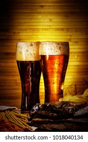 Two glasses of light and dark beer with beer snacks
