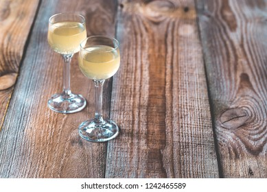 Two glasses of limoncello on the wooden background
