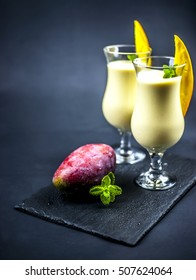 two glasses of mango lassi  with mint and mango on black background