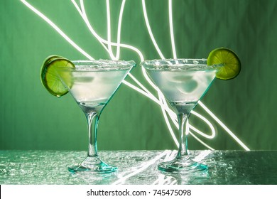 Two glasses with margarita cocktail, standing on the bar and outlined by a bright light. Club atmosphere
