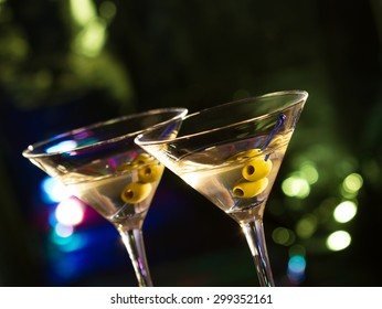 Two glasses with martini , focus on a olives