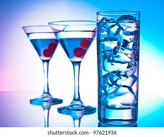 Two glasses of martini with red cherries and a glass of clear cocktail