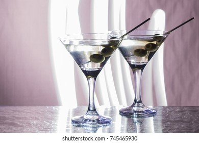 Two glasses with martini and three shots standing on the bar and outlined by a bright light. Club atmosphere