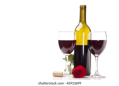 Two glasses of merlot with a bottle of wine, rose and cork ready for celebration.