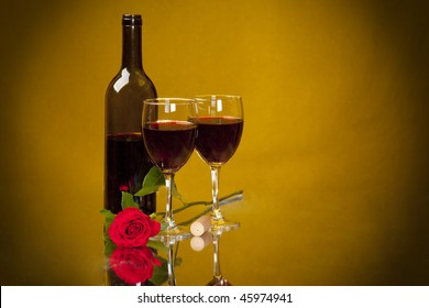 Two Glasses of merlot on a reflective mirror, with bottle, rose, and cork.