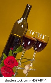 Two glasses of merlot on a reflective mirror with bottle, rose, and cork.