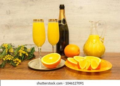 Two glasses of mimosa cocktail, a bottle of champagne, a decanter with orange juice, fresh oranges and mimosa sprig on a wooden table
