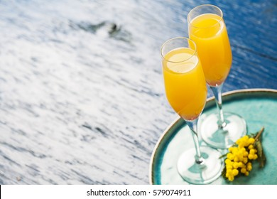 Two glasses with mimosa cocktail (sparkling wine plus orange juice)
