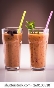 Two glasses of mixed banana, orange, blackberry smoothie with mint