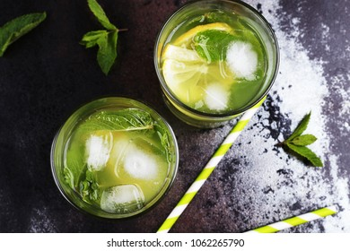 Two glasses of mojito cocktail with mint, lemon and ice on the black table. Alcohol drinks, relax concept